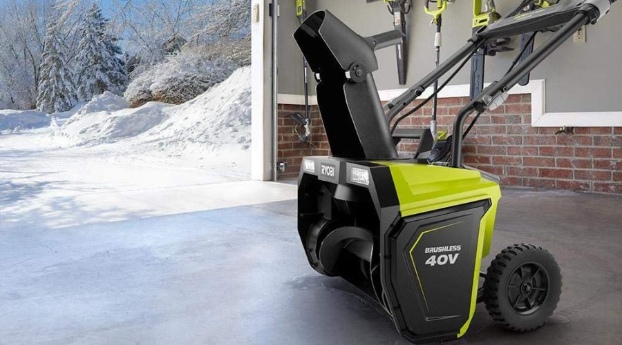 RYOBI snow blower standing in an open garage with a winter scene outdoors.