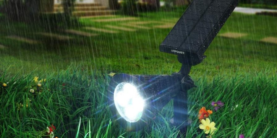 Solar light illuminating lawn with flowers as rain is pouring down.
