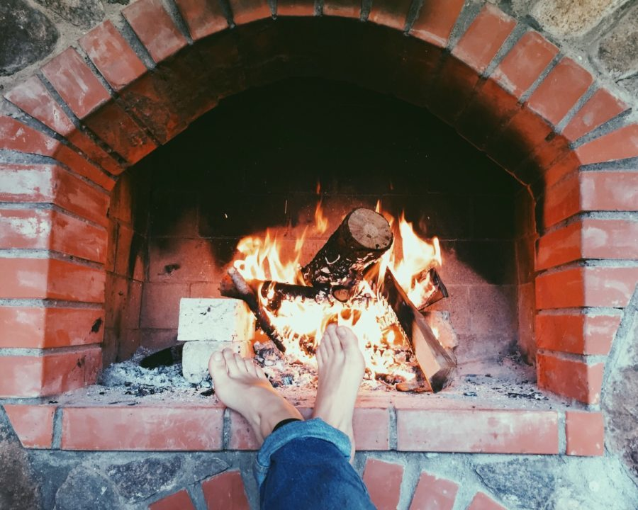 woodburning fireplace indoors with feet resting on brick