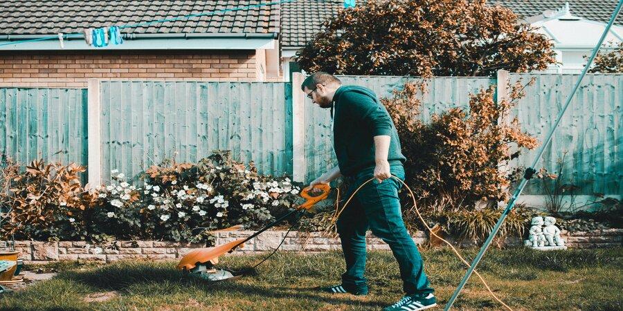 Man mowing lawn in his backyard.