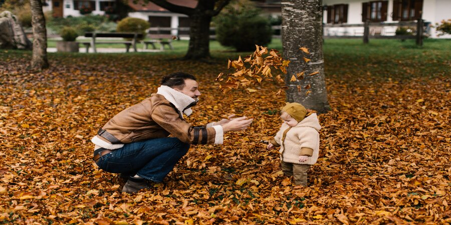 Father and child on a lawn covered in fallen leaves.