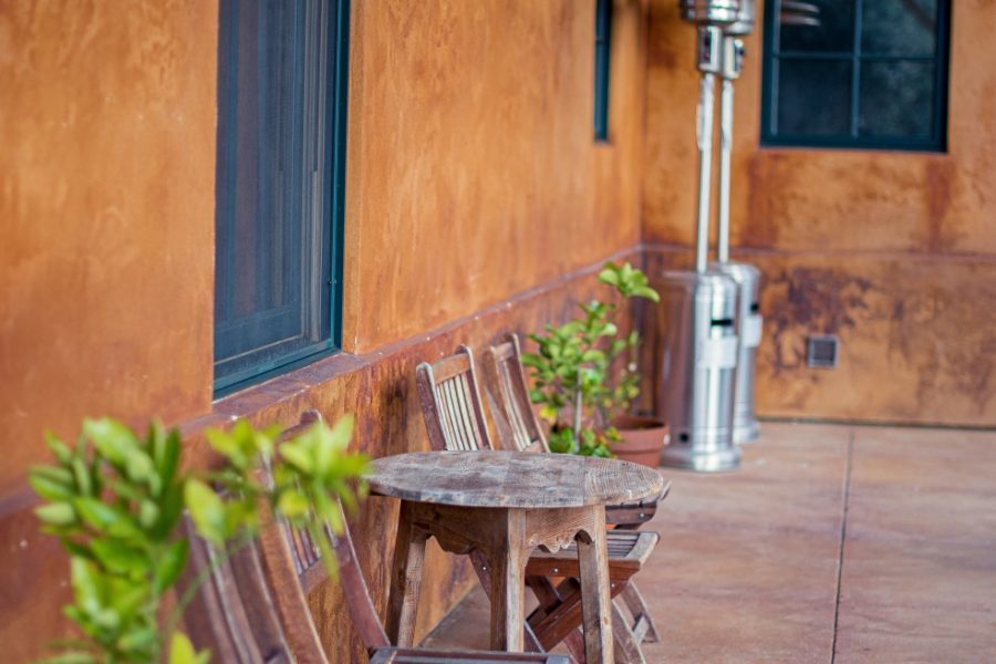 patio heaters Rustic wooden outdoor chairs and a table against orange wall