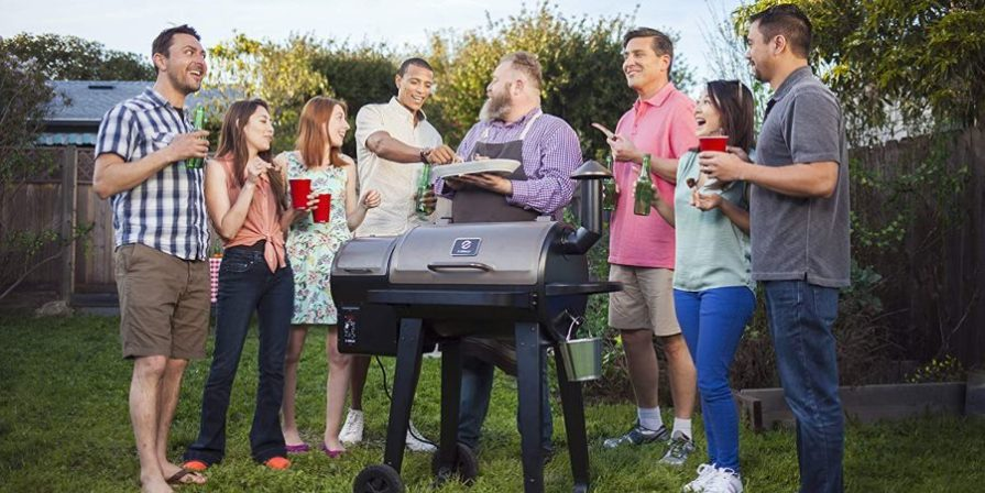 Group of people standing around a wood pellet smoker enjoying their BBQ.