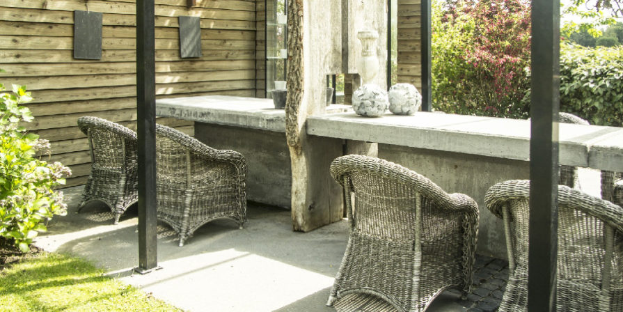 Long concrete dining table with wicker chairs.