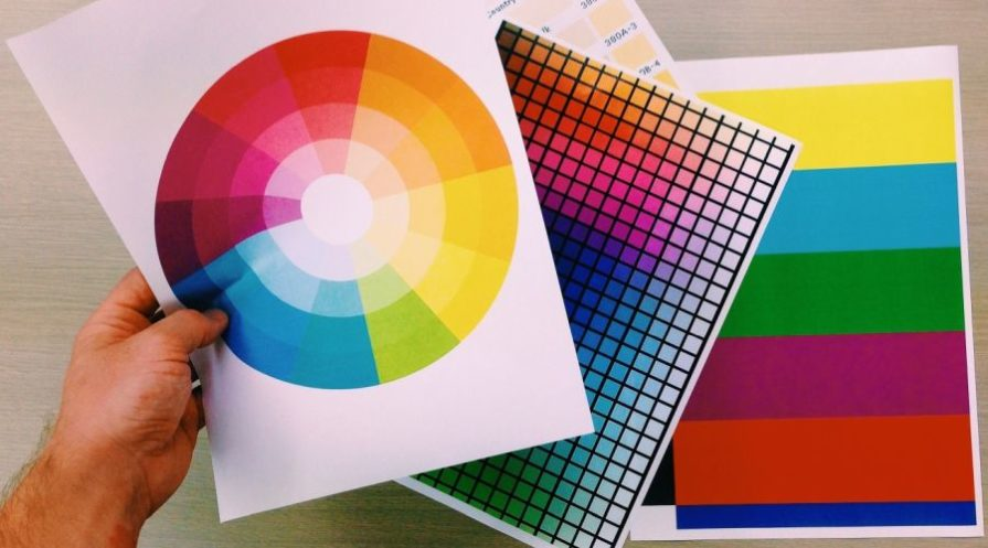 Man holding several sheets with color palettes.