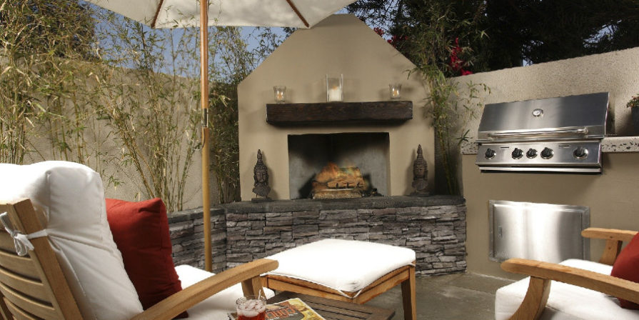 Outdoor fireplace with separate BBQ and bar next to it.