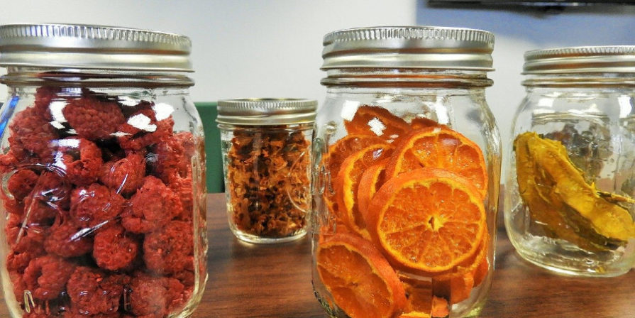 Glassed filled with dried fruit, including oranges and raspberries.