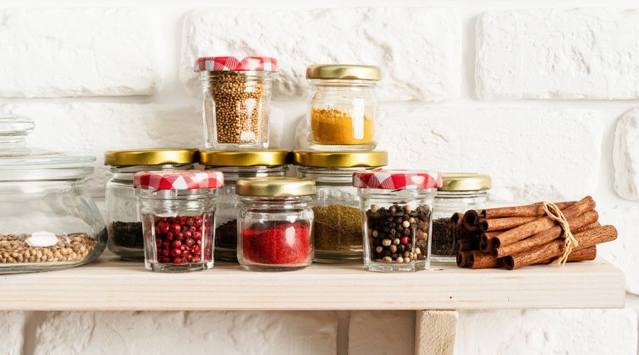 Glass jars filled with dry goods on wooden shelf in front of white brick wall.