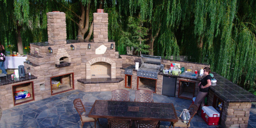 Full open-air kitchen built from stone with stone floor tiles and dining table at the center.