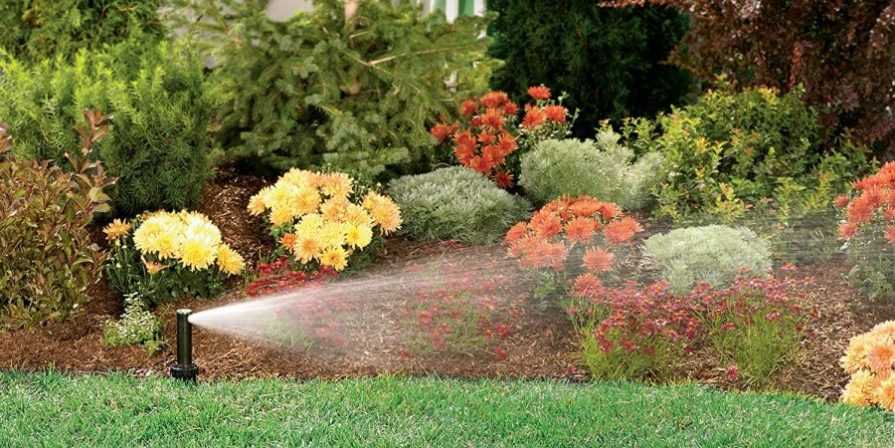 Gear-driven sprinkler spraying water over a flower bed.
