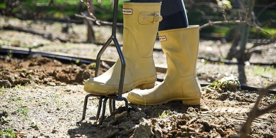 Woman with yellow boots using a hand tiller on your property.