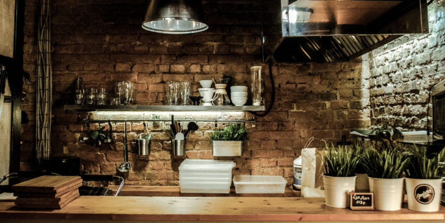 Modern kitchen built into a brick wall nook with lots of herbs standing on the wood slat working area.
