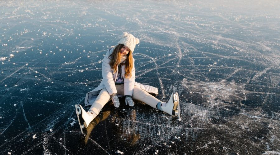 Woman with ice skates sitting on ice rink.