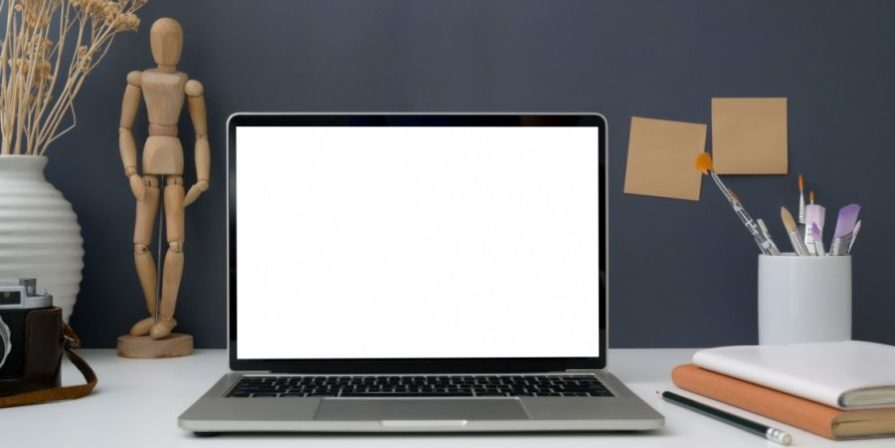 Laptop standing on desk in front of grey wall.