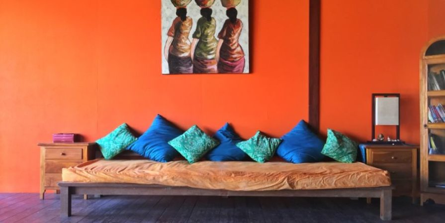 Rustic sofa in front of a bright orange wall.