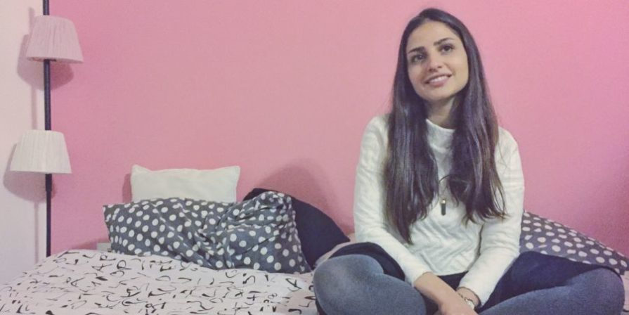 Girl sitting cross-legged on her bed with pink wall in background.