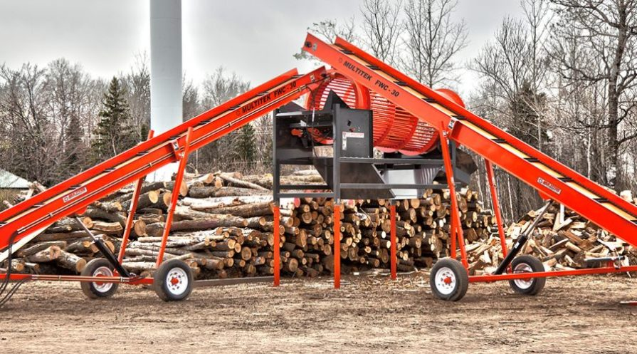 Two Multitek firewood conveyors in front of a pile of logs