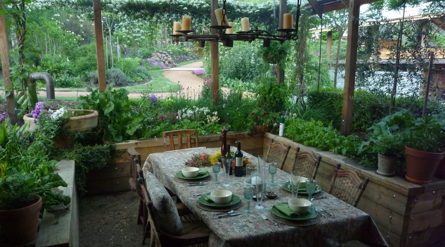 Covered outdoor dining table in a garden setting, surrounded by plants and bushes.