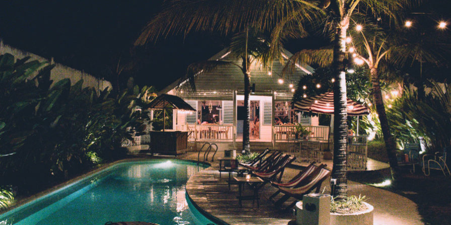 Pool with house in the background, wooden deck and beach chairs to its right side, and a small tiki bar on its far end.