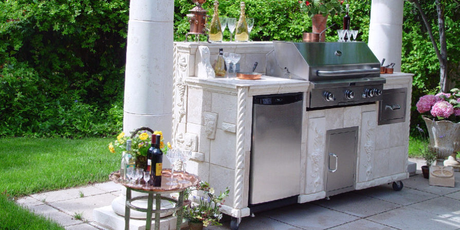 Wheeled grill station with built-in fridge, cladded in what looks like white marble.