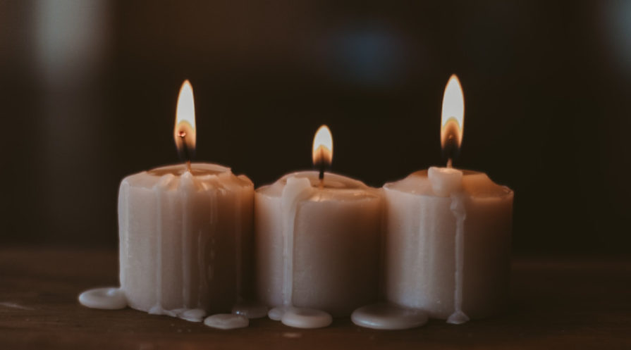 Three burning white candles with dark background.