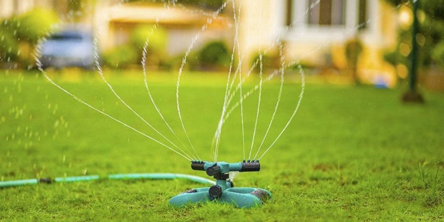 Rotary sprinkler shooting water across a lawn.