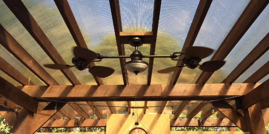 Screened wooden pergola holding a ceiling fan.