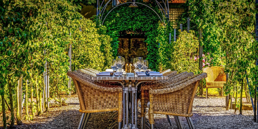 Outdoor dining table with wicker chairs, surrounded by greenery.