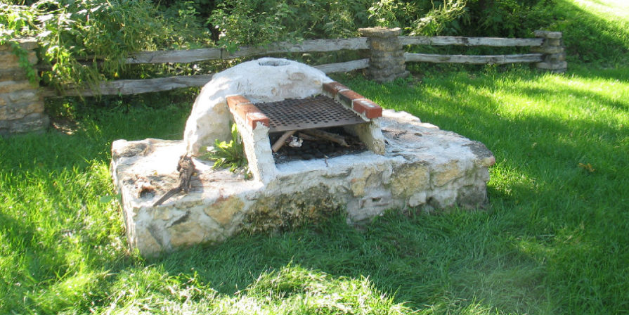 Simple stone BBQ pit on a lush green lawn.