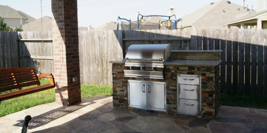 Simple built-in stone grilling station backed by garden fence.
