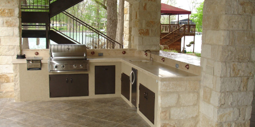 A beige stone outdoor kitchen with a built-in stainless steel grill.