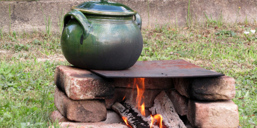 Wood burning stove built from bricks, topped with a metal sheet holding a green stoneware pot.