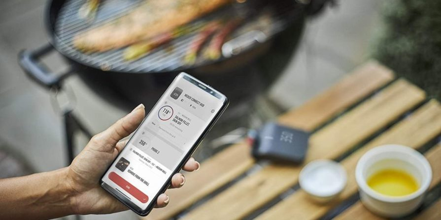 Smartphone with Weber smart grill app open and grill in the background