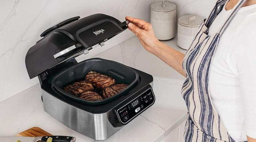 Woman opening Ninja smart grill with steaks cooking