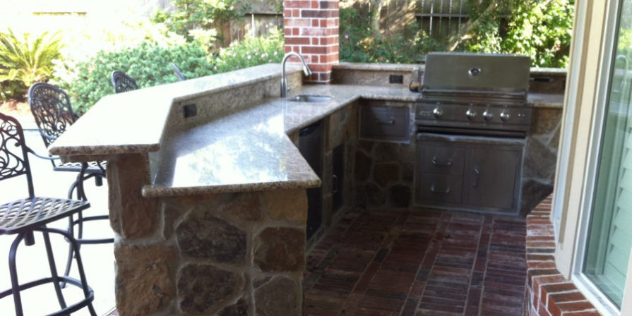 Outdoor kitchen nook with a grill, sink, and marble counter, with a raised bar for guests sitting on high chairs on the other side.