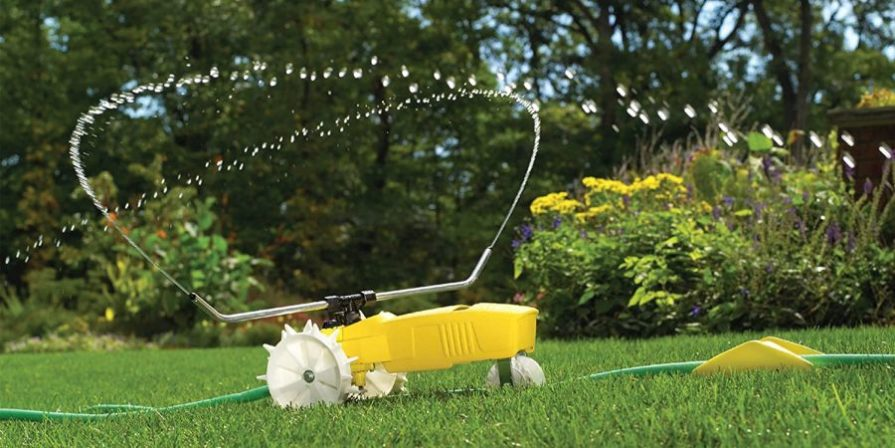 A traveling sprinkler running across a lawn, ejecting water.