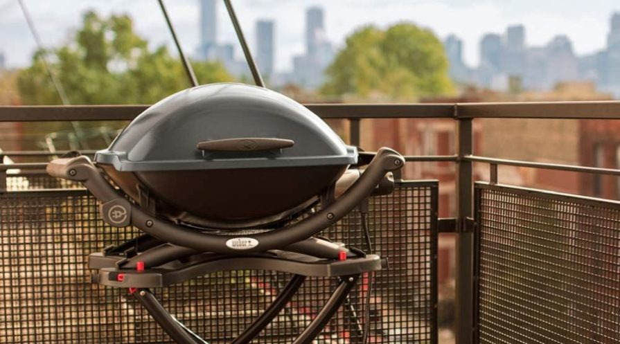 Weber grill standing on a city balcony.
