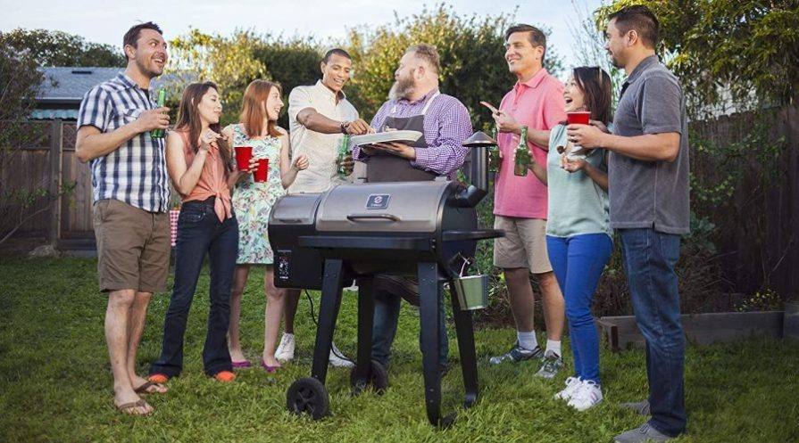 A group of family and friends gathers around a pellet smoker and grill in the backyard.