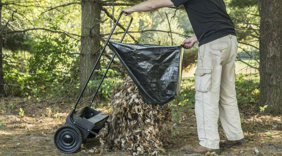 Man emptying an Agri-Fab lawn sweeper.