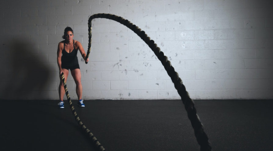 woman using battle ropes for intense workout