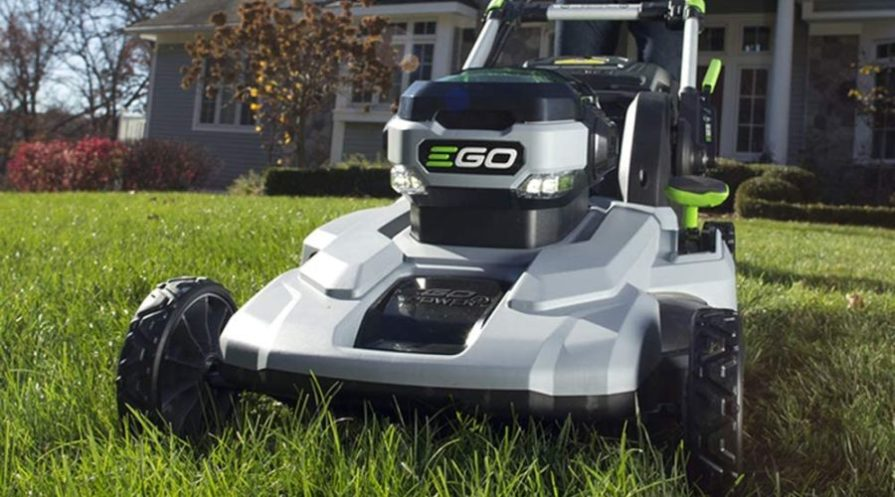 EGO Power+ lawn mower on a lawn outside a big houss.