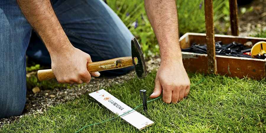 A man hammers a guidewire peg for robotic mowing navigation into the lawn.