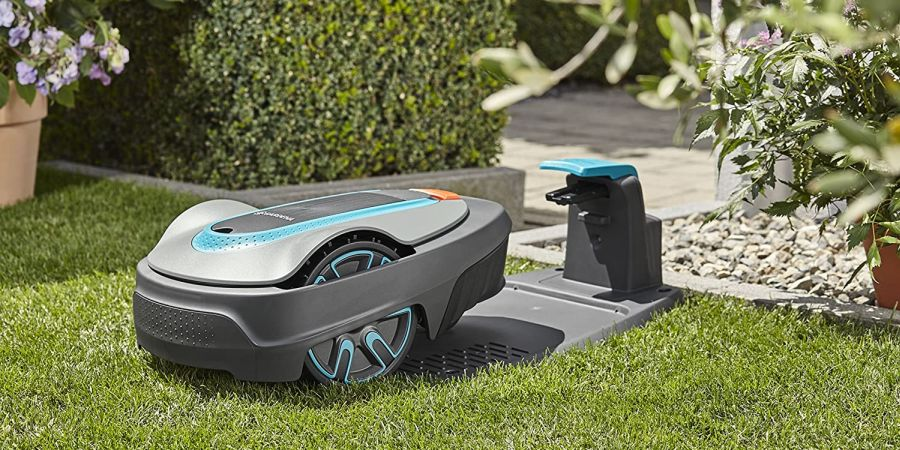 A two-tone grey robotic mower approaches its charging station.