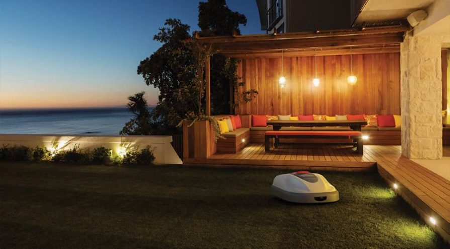 The Honda Miimo robotic lawn mower doing its job with a deck and seating area in the background.