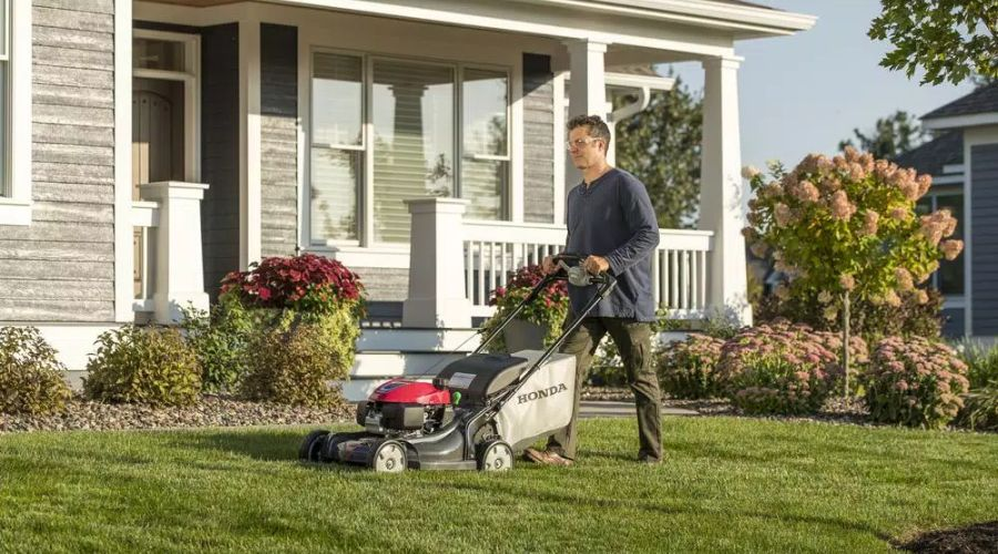 Man mowing the lawn in front of his house with a Honda NeXite lawn mower.