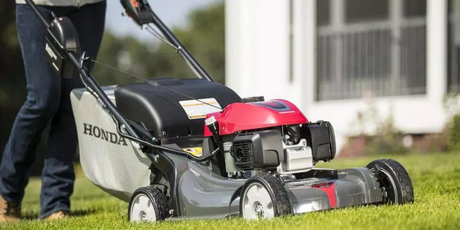 Woman mowing her lawn with a HRX NeXite self-propelled lawn mower.