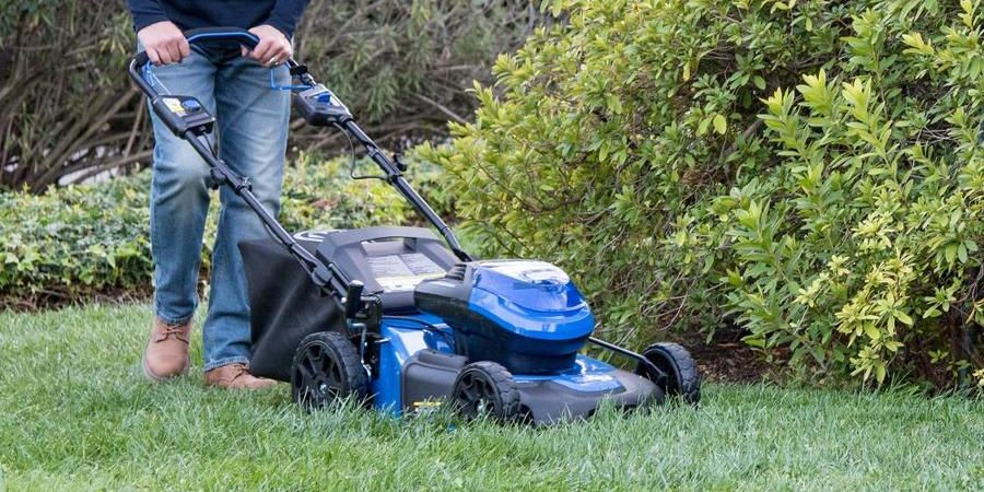 Man pushing a blue Kobalt lawn mower.