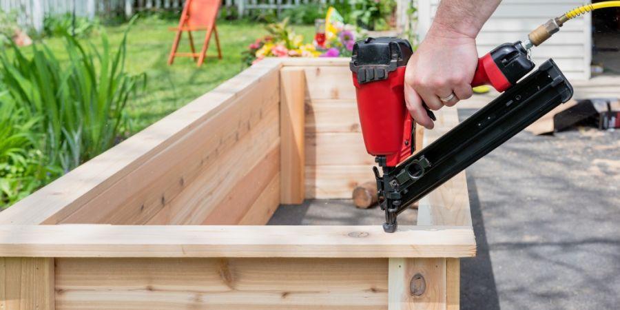 Man using a red nail gun to build a wooden garden bed.