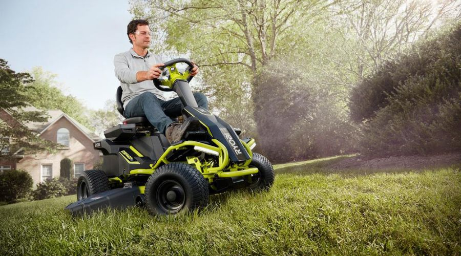 Man riding a RYOBI cordless electric lawn mower to cut the grass on his property.