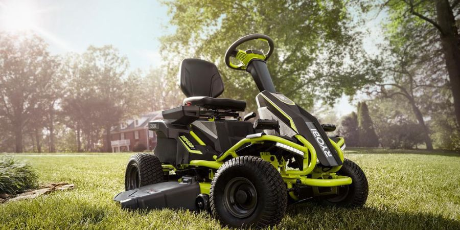 A Ryobi electric riding lawn mower parked on the lawn of a property.